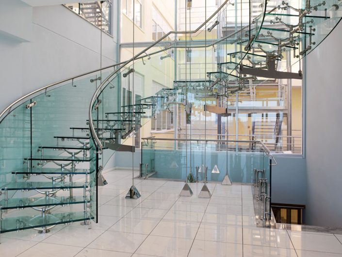 Central spine staircases feature glass stair treads curved glass balustrades